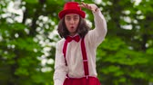 жестикулируя : Funny young mime walks on stilts and juggling in the park