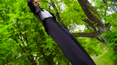 stilts : Young man in costume walks on stilts at the park Stock Footage