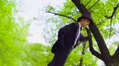 действие : Young man in costume walks on stilts in the park near tree