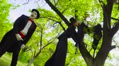 apart : Mime and street artists fooling on stilts play in the park