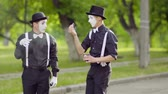 nyel : Two mimes smoking in the park together