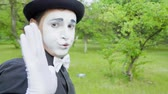 imitação : Funny mime is crooking on camera in the park