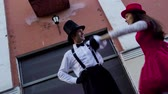 korzet : Comic couple on stilts dancind near building