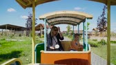 struś : Beautiful woman and little boy ride open car at the contact zoo