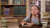 prateleira de livros : Little girl writes at a table in the library