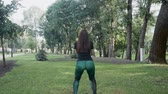 bounces : Beautiful brunette doing morning exercises in the park Stock Footage