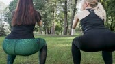 bounces : Two beautiful girls doing exercises in the park. Stock Footage