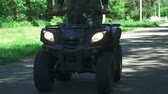 quatro pessoas : Young guy drive on the quad bike on a country road