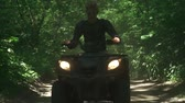 empolgante : Young man drives ATV in the forest