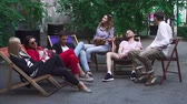 produtividade : Company of young people is resting on a summer area in a cafe Vídeos