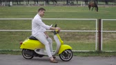 lambreta : Young guy sits on a moped and looks at the horses