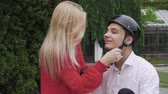 lambreta : Young girl helps to guy to put a helmet Stock Footage