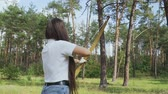 дартс : Beautiful girl takes aim with a bow Стоковые видеозаписи