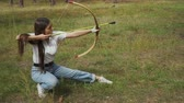 bowman : Girl shooting with bow from a sitting position