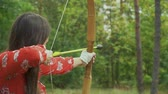 bowman : Beautiful girl aims and shoots with a bow. Close-up. Stock Footage