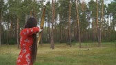 дартс : Woman in red dress practice in shooting in forest
