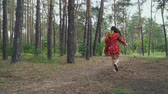 bowman : Woman in red dress with a bow running away Stock Footage