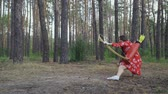 archery : oung girl in red dress shooting from a sitting position