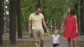těhotná : Parents hold the boys hands and walk in the park