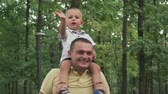 сердцебиение : Little boy sitting on the shoulders of his father waving