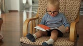 сердцебиение : Little boy sits with a book on a chair Стоковые видеозаписи