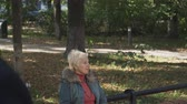 argumento : Adult man walks by an adult woman sitting on a bench. Stock Footage