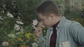 hombre gay : Feminine guy sniffs flowers