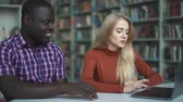 uczeń : African american and european blonde chatting and looking at a laptop