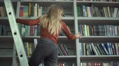 levantarse : The female is trying to get the book from upper shelf in the library