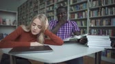 zusammensetzen : African american male and european female fall asleep in the library Stock Footage