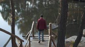 jangada : Brutal bearded man walk to a lake by bridge witn an axe in his hand. Young bearded guy with an axe outdoors. Stock Footage