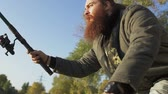 solitário : Fisher with long beard fishing on the river bank. Fisherman emotionally waiting for the fish. River fishing. Stock Footage