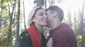 ırklararası : Young smiling couple in love kissing on a background of pine trees and sunset light. Multi ethnic couple in love. Stok Video