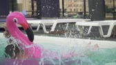 inflável : Young funny guy have fun at weekend and jump on inflatable flamingo, creating splashes in swimming pool Vídeos