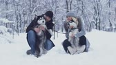 忠実な : Attractive young couple holds and hugs two beautiful siberian huskies and scratches their fluffy bellies. Dogs on a winter walk in the forest.