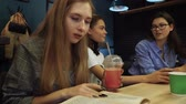 учебник : While two friends communicate and chat, the third sits, leafs through the book and drinks fresh lemonade