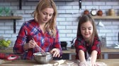 orgulhoso : Young mother with blond long hair mixing in plate and small cute naughty girl play with flour on the kitchen table