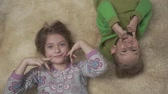 irmãs : Cute little kids in pajamas lying on the floor with fluffy carpet. Brother and sister touch face. Happy siblings weekend.