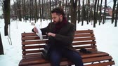 literário : Bearded man sitting on the banch in the winter park. Businessman opens his case and gets book