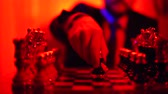 kraliçe : Close-up of the hand of a man in a business suit sitting on a blurred background playing chess. Stok Video