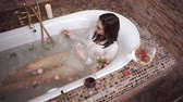 knocking : Cute sensual woman in white shirt taking a bath. Water flows from the water tap. Cute girl enjoying in the bathroom with burning candles, wine and goldfish in a bowl aquarium