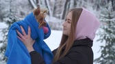 jorkšírský : Portrait young girl kissing a yorkshire terrier in a winter snow-covered park holding a dog wrapped in a blue blanket. A teenager and a pet on a walk outdoors. Slow motion.