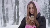 štěně : Portrait smilling cute girl with long hair hugging a yorkshire terrier dressed in wool sweater holding dog on hands in a winter snow-covered park. Teenager and a dog on a walk outdoors. Snowing.