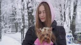 jorkšírský : Portrait smilling cute girl with long hair hugging a yorkshire terrier dressed in wool sweater holding dog on hands in a winter snow-covered park. Teenager and a dog on a walk outdoors. Snowing.