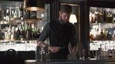 rozdrtit : Tall bearded bartender crushing big piece of ice with the knife standing at the bar counter. Barman making cocktail in modern bar with many bottles on shelves