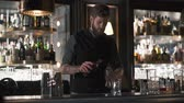 пьяный : Hipster bartender mixologist combining ingredients and making a whiskey cocktail in beautiful modern bar. Slow motion