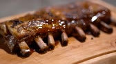 szolgáló : Close up just cooked juicy fragrant fried ribs watered with barbecue sauce. Beautifully serving on wood desk.