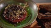 ケーパー : Raw tartar with ingredients filled with olea, lying in a clay plate on a table next to black toasted bread close up.. The camera moves from left to right. 動画素材