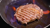 browned : Juicy piece of grilled meat frying on pan burning close up. Fire is in the frying pan