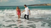 panties : Dressed man and woman standing in shallow sea water. Girl raising her dress a little, panties are visible. Leisure of young family. Beautiful seascape. Image zooms Stock Footage